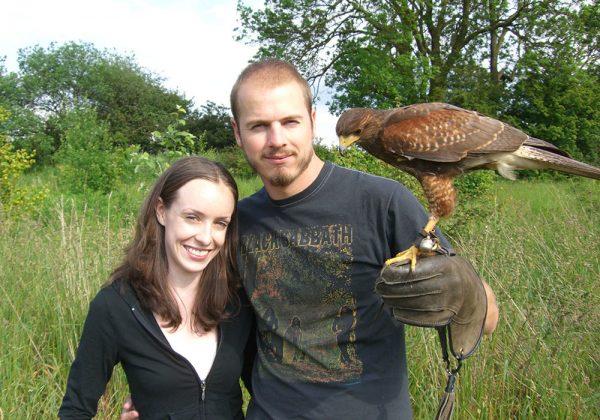 Couple holding Harris Hawk